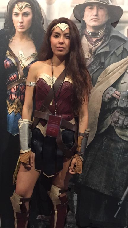 hero's wonder woman poses in front of a photo from the 2017 movie at Warner Bros. Studios